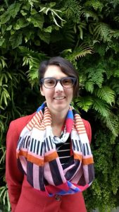 Kate stands in front of wall of green ferns. She has short brown hair, blue glasses and wears a red blazer and striped scarf.